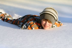 Boy lying in the snow stock images