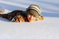 Boy lying in the snow royalty free stock image
