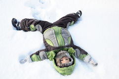 Boy lying on snow Royalty Free Stock Photos