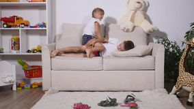 The boy is lying on the sofa, and the girl is running around the room stock video footage