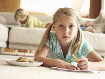Boy lying on sofa at home, focus on girl (6-8) lying on floor with paper and biscuits, surface level Royalty Free Stock Photo
