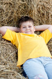 Boy lying on  straw Stock Images