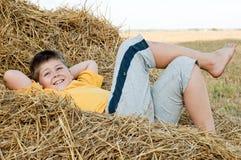 Boy lying on  straw Stock Photos