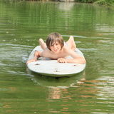 Boy lying on a surf. Angry little boy in grey shorts lying on surf board Royalty Free Stock Photo