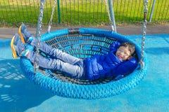 Boy lying on swing at palyground Stock Image