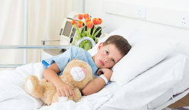Boy lying with teddy bear in hospital Stock Photography