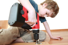 Boy lying and tightening screws in board Royalty Free Stock Photos