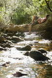 Boy Lying On Tree Trunk By Stream. Full length of teenage boy lying on tree trunk by stream in forest Stock Photos