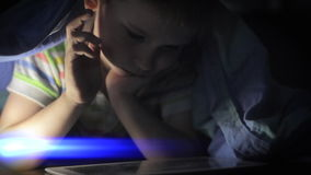 Boy lying under blanket and watching cartoon on touch pad stock footage