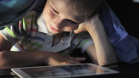 Boy lying under blanket and watching cartoon on touch pad stock video footage