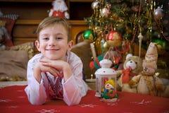 Boy lying under Christmas tree Stock Photo