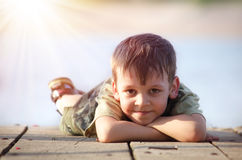 Boy lying on a wooden platform Royalty Free Stock Image