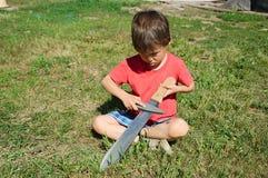 Boy machete edge sharpening Stock Photo