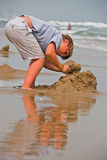 Boy made sandcastle on beach Royalty Free Stock Image
