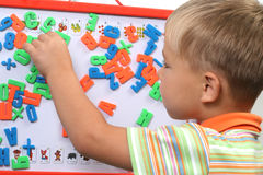 Boy with magnet letters stock photo