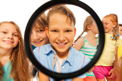 Boy through magnifier glass and with friends Royalty Free Stock Photography