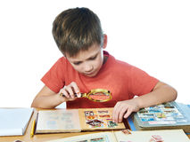 Boy with magnifier looks his stamp collection isolated Royalty Free Stock Photo