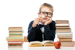 Boy with magnifier at the table with a pile of books on a white Royalty Free Stock Photography