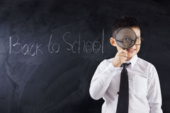 Boy with magnifier and text Back to School. Male primary school student looking through magnifier with text Back to School on the blackboard Royalty Free Stock Photo
