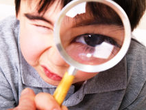 Boy and magnify glass. Looking at camera Royalty Free Stock Photos
