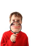 Boy and magnify glass. Isolated on the white background Royalty Free Stock Photo