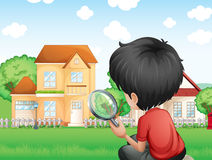 A boy with a magnifying glass studying the grasses Stock Photos