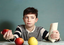 Boy make choice between  apples and fast food Stock Photography