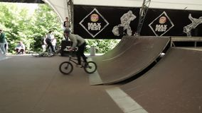 Boy make extreme flip on BMX bicycle in skate park. Summer. Audience. stock footage