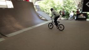 Boy make extreme flips on BMX bicycle in skate park. Summer. Audience. stock video footage