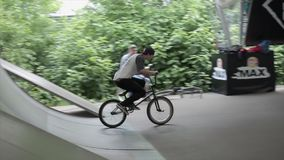 Boy make extreme triple flips on BMX bicycle in skate park. Summer. Slow motion stock video footage