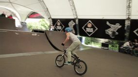 Boy make extreme turnover on BMX bicycle in skate park. Summer. Audience. stock video