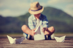 Boy make a paper boat sitting on the wooden pier Royalty Free Stock Images