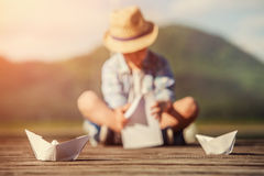 Boy make a paper boat sitting on the wooden pier Stock Photo