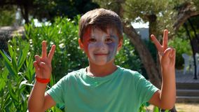 Boy with make-up in form of a French flag. Boy is a fan of the french team, with make-up in the form of a french flag. Boy shows a peace sign stock footage