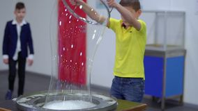 Boy makes a big bubble. With soap water and special ring. The boy moves away from the bowl with soapy water and creates big colorful bubble. The museum of stock video footage