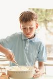 Boy makes a cake in kitchen Stock Photography