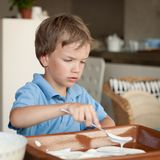 Boy makes a cake in kitchen Royalty Free Stock Image