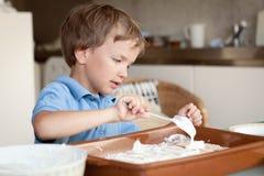 Boy makes a cake in kitchen Stock Photos