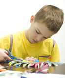 The boy makes crafts. Stock Images