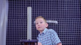 Boy makes experiment with electromagnetic equipment in science museum. Children have an experiment with electromagnetic fountain. The boys put metal ring on the stock video footage
