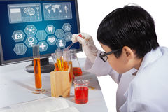 Boy makes experiments with monitor on desk. Little boy making chemical experiments using chemistry liquid in test tube with computer on desk Royalty Free Stock Photos