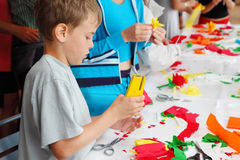 Boy makes flower of tissue paper by stapler. Boy makes artificial flower of tissue paper by stapler near table and other people royalty free stock photography