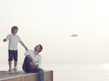 Boy makes fly his paper airplane with his father`s help stock images