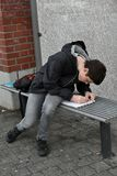 Forgotten school homework. Boy makes forgotten homework in the morning at the school bus stop Stock Images