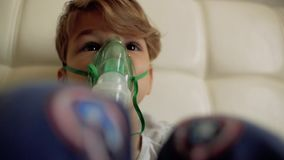 The boy makes inhalation while sitting on the bed.the child inhales steam stock video