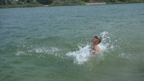 Boy makes a jump in the lake stock footage