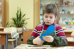 Boy makes a masquerade mask in class at school Stock Photo