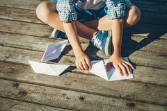 Boy makes paper boats on wooden pier Royalty Free Stock Photo