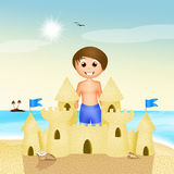 Boy makes sandcastle Stock Image