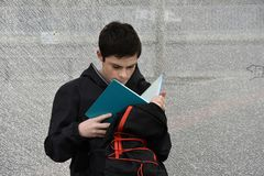 Boy makes school homework at the bus stop, he learns vocables. Boy makes forgotten homework in the morning at the school bus stop, he learns vocables royalty free stock photo